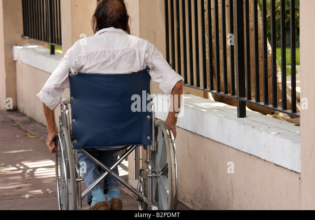 Miami Beach Florida Washington Avenue man long hair wheelchair sidewalk push wheels handicap disabled physical impairment - Stock Image