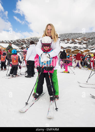 Mother and small child in skiing clothes on skis  prior to a skiing lesson with slopes  and chalets behind - Stock Image
