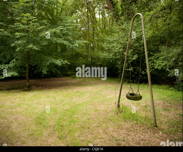 Lonely tyre swing in a wooded glade - Stock Image