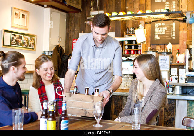 Young man shows variety of beer brands to friends in pub, Dorset, Bournemouth, England - Stock Image