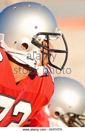 American football player wearing red football strip and protective helmet, close-up, profile, focus on foreground - Stock Image