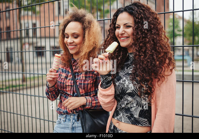 Cheerful young girls eating candy ice cream. Two young women standing against a fence smiling, outdoors. - Stock Image