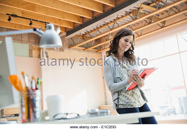 Businesswoman working in new office - Stock Image