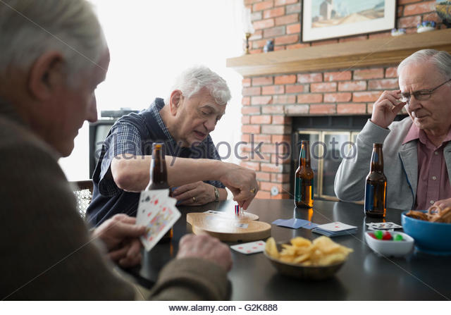 Senior men playing cribbage and drinking beer - Stock Image