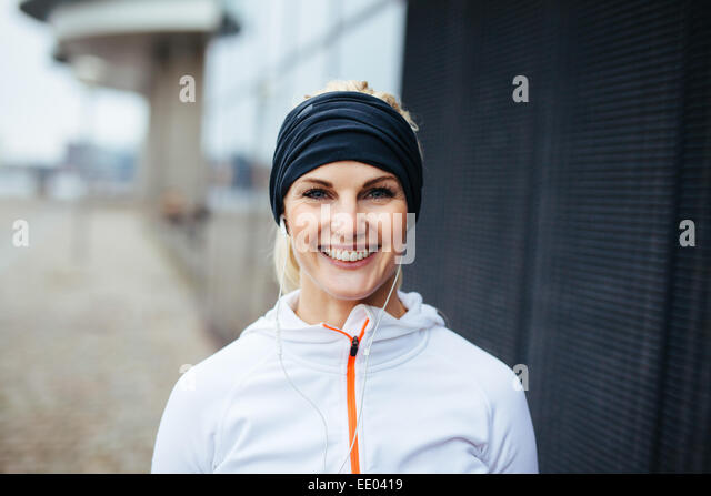Portrait of cheerful young fitness woman. Smiling young female athlete in sports wear outdoors. - Stock Image