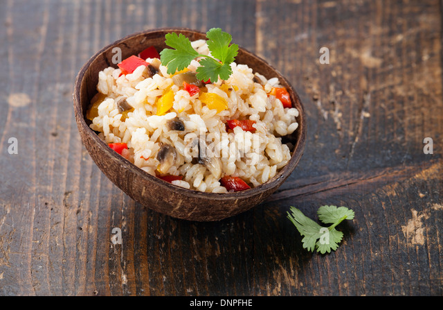 Rice with vegetables in wooden bowl - Stock Image
