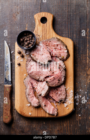 Roast beef on cutting board with salt and pepper - Stock Image