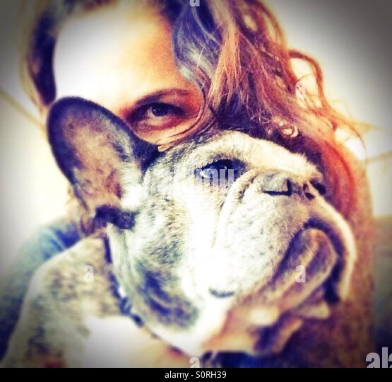 A woman and an old French bulldog. - Stock Image