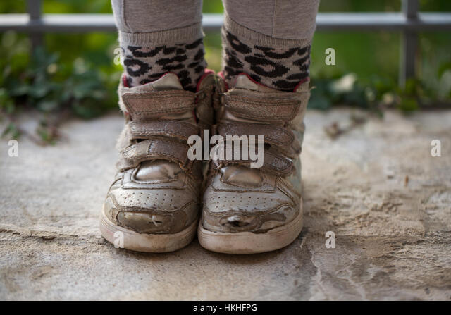 low section of a person wearing damaged shoes. torn, boot, weathered, wet. - Stock-Bilder