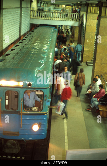 Russia former Soviet Union Moscow underground Metro subway system station boarding passengers - Stock Image
