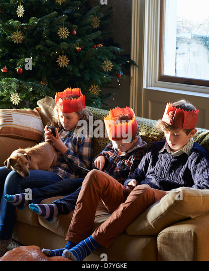Children in paper crowns relaxing on sofa - Stock-Bilder