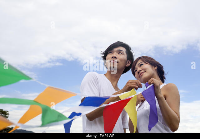 A couple, a man and woman in a Kyoto park holding up a colourful row of flags. - Stock Image