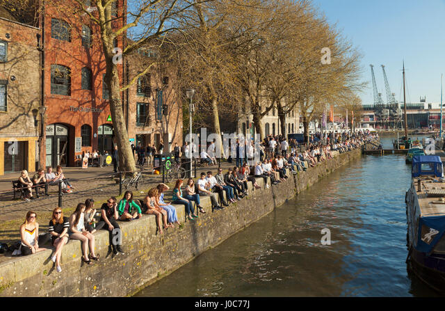 Young people enjoying the evening sunshine at Saint Augustine's Reach quayside, Bristol. - Stock Image