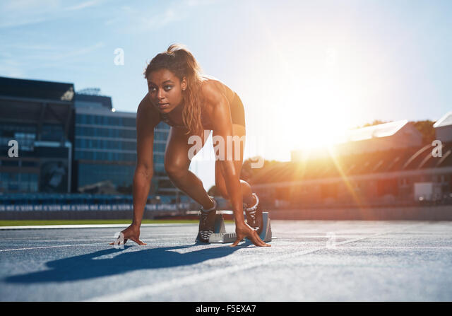 Confident female athlete in starting position ready for running. Young woman about to start a sprint looking away - Stock Image