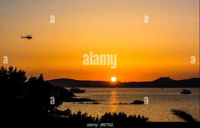Hovering helicopter watching a fabulous orange sunset over Sardinia, Italy - Stock Image