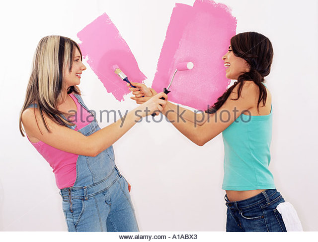 Two women painting wall - Stock-Bilder
