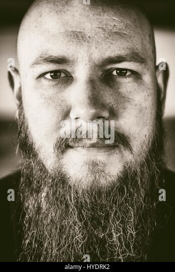 Bald man with long beard stares into camera. - Stock Image