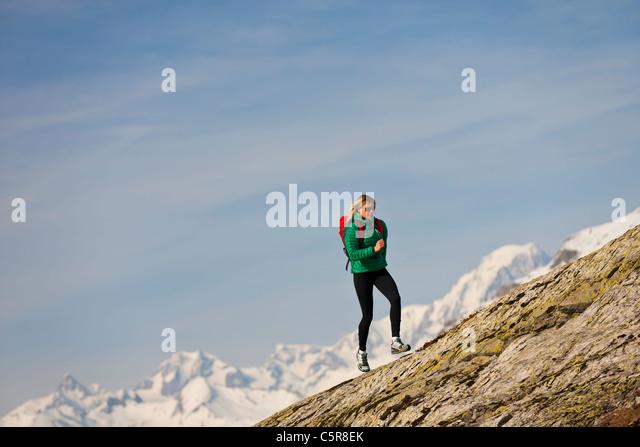 A runner runs over a rocky mountain. - Stock-Bilder