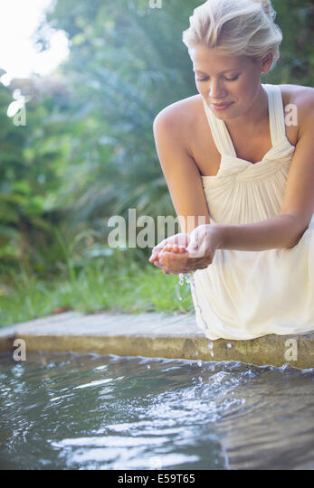 Woman cupping pool water in her hand - Stock Image