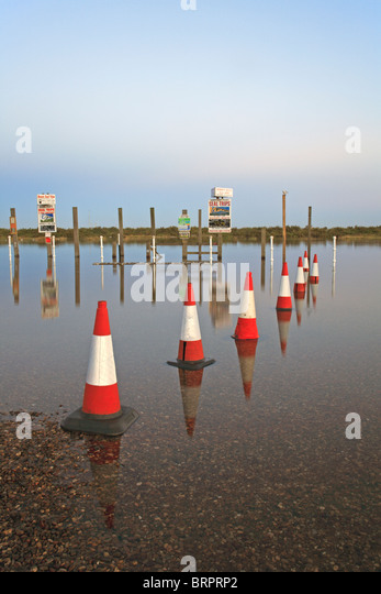 Traffic cones and reflections as a spring tide overflows the harbour wall into the car park at Blakeney, Norfolk, - Stock Image