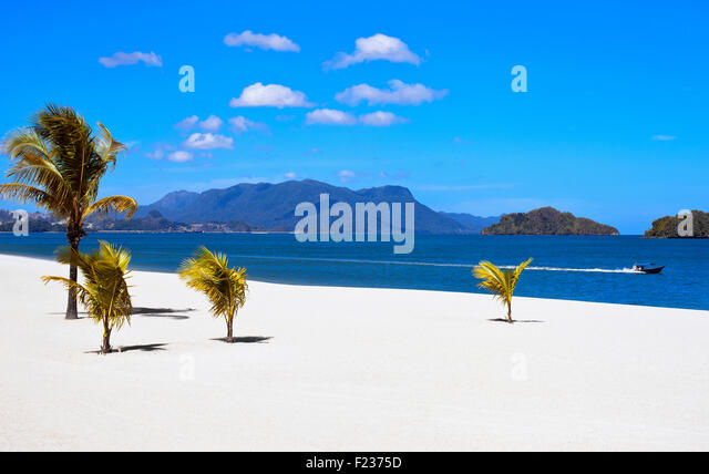 A motor boat speeds along the private beach fronting the Royal Villa at Four Seasons Langkawi,Malaysia - Stock Image