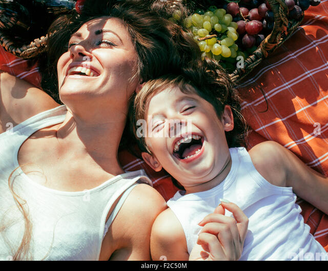 cute happy family on picnic laying on green grass mother and kids, warm summer vacations - Stock Image
