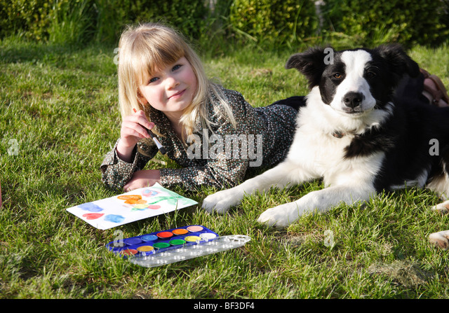 Child paint with her dog in the garden - Stock Image