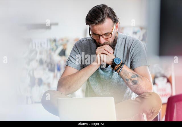 Pensive male design professional working at laptop - Stock-Bilder