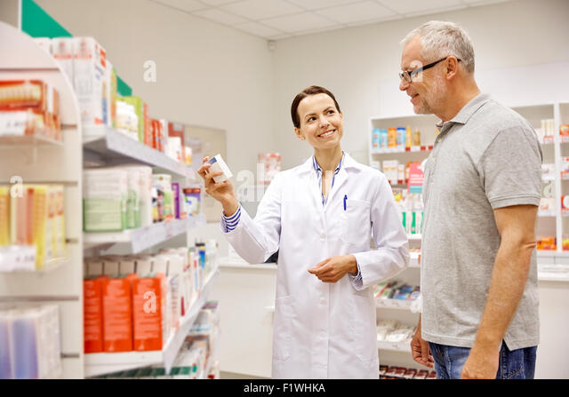 pharmacist showing drug to senior man at pharmacy - Stock Image