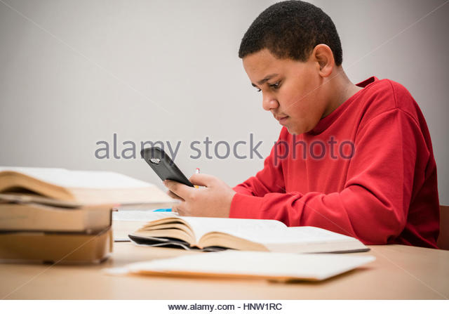 Teenage boy studying with textbooks texting on cell phone - Stock-Bilder