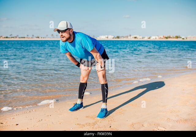 Mid adult man on coastline bending forwards looking away, Dubai, United Arab Emirates - Stock Image