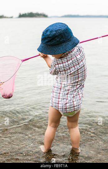 Sweden, Sodermanland, Stockholm Archipelago, Musko, Boy (2-3) standing in water with fishing scoop - Stock Image