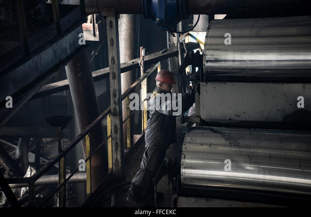 A worker carries out repairs to coal pressing machinery - Stock Image