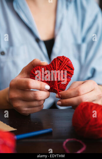 Woman creating red woolen heart - Stock-Bilder