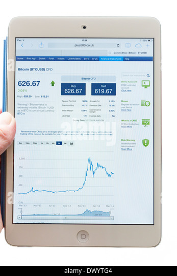 Person holding an iPad mini tablet whilst looking at Plus500 website quoting bitcoin exchange rate and trading prices - Stock Image