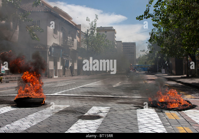 Burning tyres as roadblocks in Quito, Ecuador, resulting from protests from police over pay - Stock Image