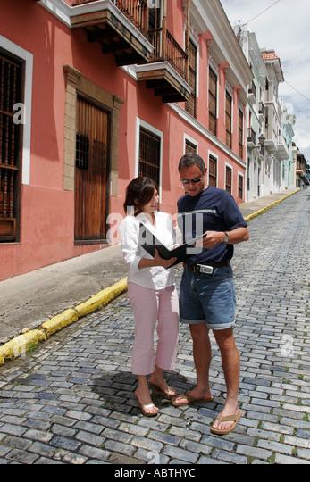 Puerto Rico Old San Juan Calle de la Cruz Hispanic female real estate broker male buyer blue adoquine stones - Stock Image