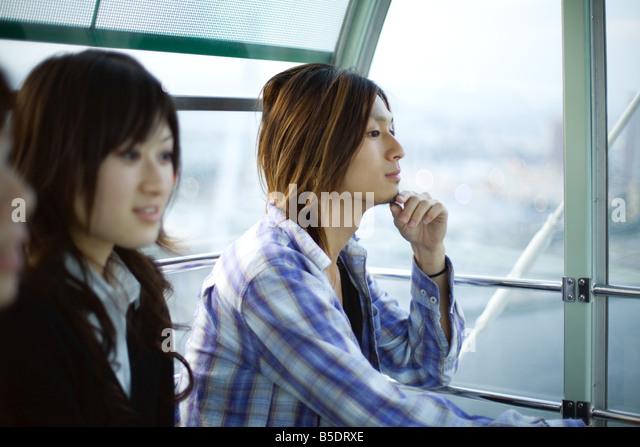 Friends taking ride on Ferris wheel at Tempozan Harbour Village, Osaka, Japan - Stock Image