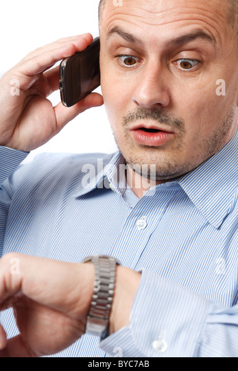 Young businessman worried looking at his wrist watch - Stock Image