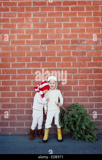 Brother and sister picking christmas tree - Stock Image