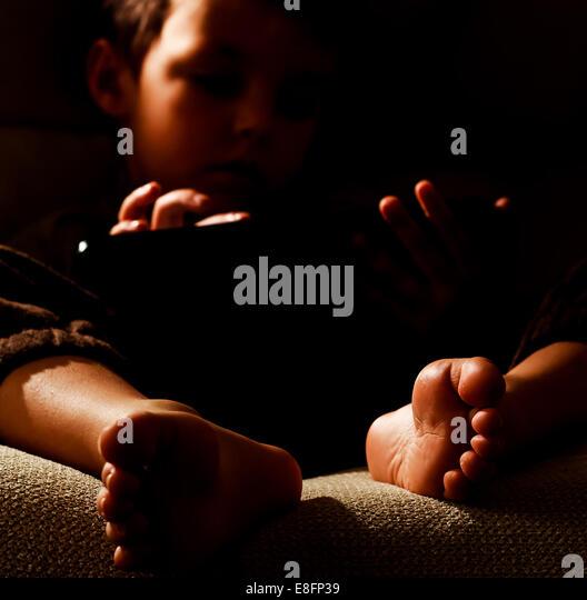 Portrait of boy (2-3) using digital tablet - Stock Image