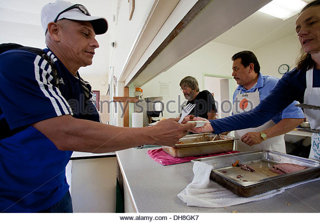 Day laborers get food and eat lunch at the Multicultural Institute in Berkeley, which provides food programs for - Stock Image