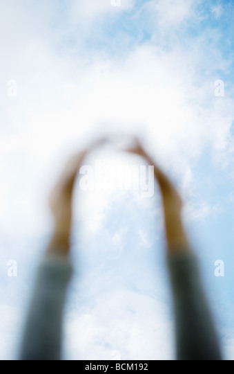 Arms reaching for sky, focus on sky in background - Stock Image
