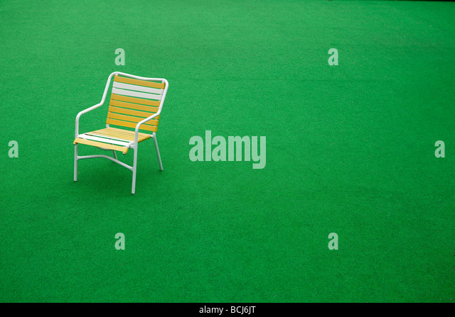 Yellow and white striped patio chair with white frame sitting on field of artificial grass Buellton California USA - Stock Image