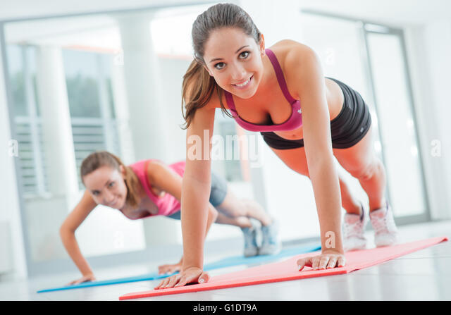Young women at the gym doing push ups on a mat, fitness and healthy lifestyle concept - Stock-Bilder