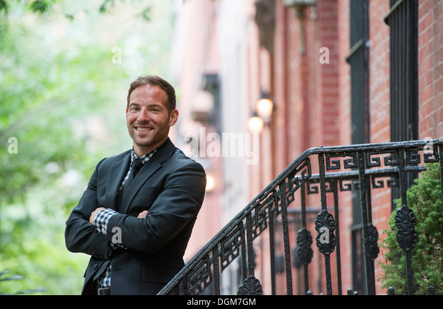Business people. A man in a suit on the steps of a brownstone building. Arms folded. - Stock Image