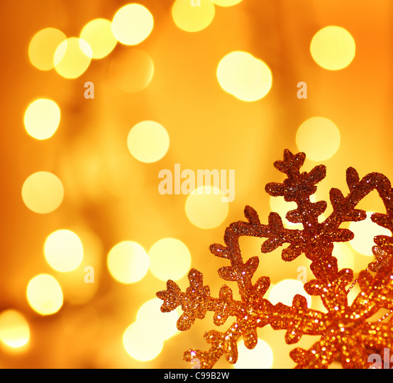 Snowflake background border golden Christmas tree ornament and holiday decoration over abstract defocus lights - Stock Image
