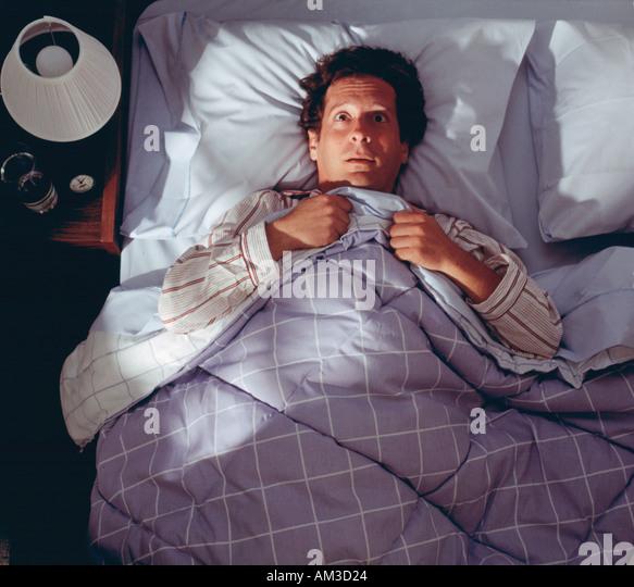 man awake in bed not sleeping, worried - Stock Image