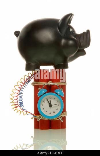 Piggy bank on a bomb, symbolic image for risky savings - Stock Image