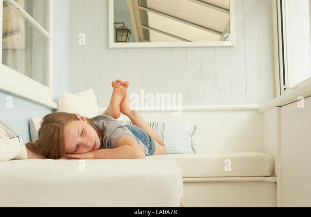 Sullen girl lying on holiday apartment seat - Stock Image